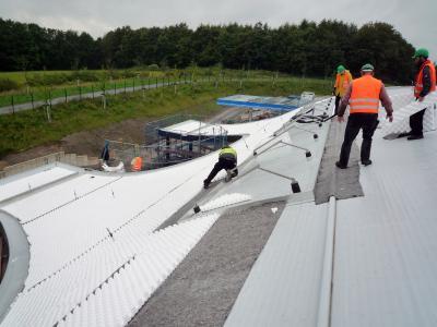 Speicherschutzmatte und schubabtragendes Dränageelement werden verlegt, der Bereich für die Sonnenkollektoren bleibt frei. Quelle: GRÜN + DACH / ZinCo