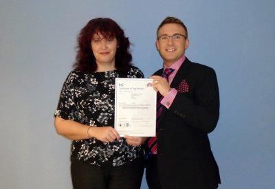 Abgebildet: Robert Park und Alison McCay von Morgan mit der AS9100 Akkreditierungsurkunde der Firma