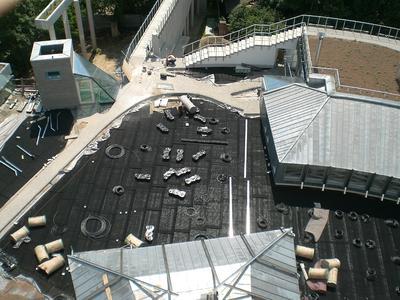 Der Blick auf die Bauphase zeigt die zeitlichen Abläufe: während die obere Dachfläche bereits fertig begrünt ist, sind unten gerade die Belagsarbeiten im Gange.