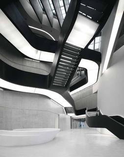 Das sanfte Licht strahlt nicht nur nach unten, sondern diffundiert durch die Gitteroste der Stufen und Stege auch nach oben. Verdeckt in den Handläufen angeordnete Lichtbänder begleiten als indirekte Beleuchtung  die Treppen