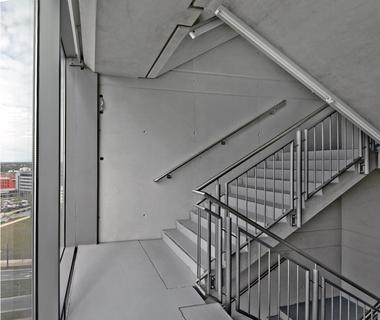 Das Treppenhaus als Notabstieg neben den Aufzügen ist sehr schlicht gehalten. Die Sichtbetonwände wurden mit Caparol Antik Lasur beschichtet