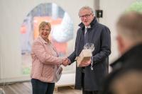 Mendens stellvertretende Bürgermeisterin Brigitta Erdem überreicht Bürkert-CEO Heribert Rohrbeck beim Spatenstich ein Geschenk