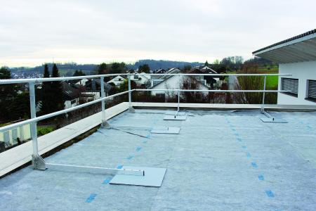 Installed safety railing prior to the installation of the green roof, which then provides the necessary ballast.