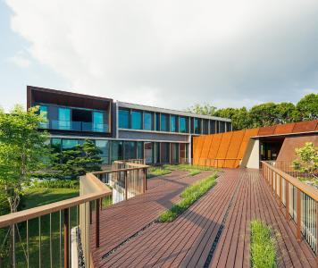 Die Anordnung der unterschiedlichen Gebäudeelemente nimmt die Hanglage und die Rautenform des Grundstücks auf. Im Bild die Fassade des Gebäudes mit den Besucherzimmern. Sie kombiniert die Systeme Schüco ASS 50.NI und Schüco ADS 65.NI mit auskragenden vertikalen Sonnenschwertern. Bildnachweis: Khoo Guojie, Singapur