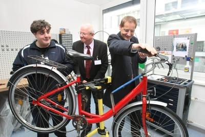 v.li.: Christian Friede zeigt Martin Zeller (Geschäftsführer Oberland Werkstätten) und Claus Haberda (Werkleiter Roche) wie er eines der 800 Roche Werkfahrräder repariert