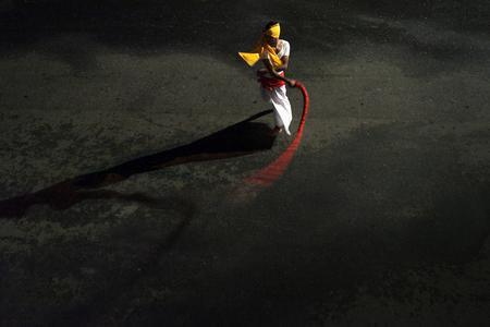 Dynamik pur, betont durch die reduzierte Farbgebung. Der traditionell gekleidete Peitschenknaller aus Kandy, Sri Lanka, fesselt den Blick des Betrachters und zieht ihn in das Geschehen / Foto: Shantan Kumarasamy