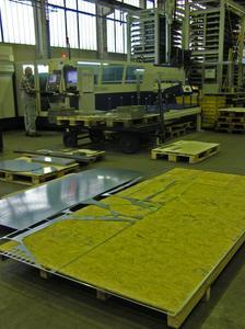 Das Ausgangsmaterial wird optimal genutzt: Von einer ursprünglich etwa 2 x 4 m großen Blechtafel bleiben nach der Verarbeitung an der Schneidanlage (Hintergrund) nur minimale Restflächen übrig