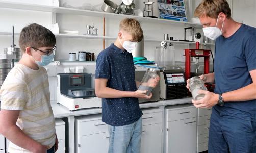 IMFAA-Mitarbeiter Benjamin Uhl zeigte im Pulverlabor wie Metalle gemahlen werden können und experimentierte mit den Schülern Johannes Memmert (links) und Benjamin Vollprecht (rechts) zum Thema additive Fertigung aus Metallen