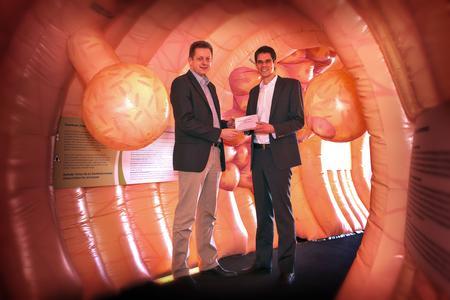 Dr. Henrik Mertens, leitender Betriebsarzt und Felix Farrenkopf, betrieblicher Gesundheitsmanager bei Heraeus mit dem Darmkrebsvorsorgetest im größten begehbaren Darmmodell Europas