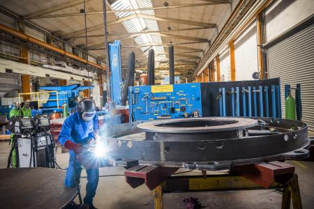 Heften und Schweißen von Kehl- und V-Nähten am Glühsockel einer Haubenofenanlage in PA und PF. Die Stahl/Stahl und Stahl/CrNi-Verbindungen erfordern unterschiedliche Zusatzwerkstoffe, die beide gleichzeitig in dem Schweißgerät verfügbar sind, Foto: EWM AG