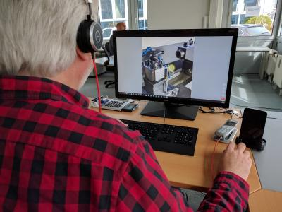 Ein Servicemitarbeiter führt von seinem Schreibtisch eine Problemanalyse an der Maschine durch und leitet den Mitarbeiter vor Ort durch den tele-Punkt an.