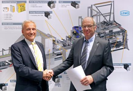 Norbert Scholz, managing director of Baumüller Anlagen-Systemtechnik GmbH (left) and Willi Fenninger, managing director and owner of LEMO Maschinenbau GmbH, seal their partnership for the new film bag machine at Interpack 2017 in Düsseldorf