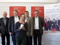 BU (hinten, v.l.n.r.) Dr. Gerd Küchmeister (FH Kiel), Dr. Dirk Müller (WTSH), Prof. Klaus Lebert (Vizepräsident FH Kiel), Michael Kopp (Wirtschaftsministerium), (vorne) Nadine Sydow, Preisträgerin Ideenwettbewerb 2014