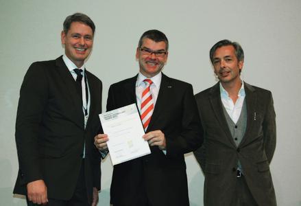 Robert Metzger, Geschäftsführer MunichExpo GmbH (links) und Vorsitzender der Jury Christian Labonte (rechts) überreichen Gunter Streng, Leiter Entwicklung Produktbereich A bei ebm-papst Mulfingen GmbH & Co. KG die Auszeichnungen