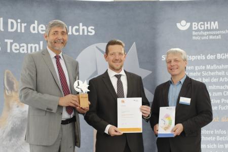 """Ralf Heinrici (BGHM), Olaf Oppermann (GS-Gabelstaplerservice GmbH) und Andreas Franzki (BGHM) bei der Übergabe der Trophäe """"Schlauer Fuchs"""" (v.l.n.r.)"""