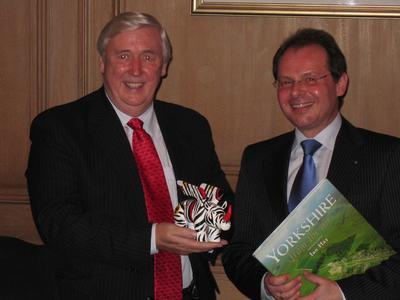 v.l.n.r.: Less Carter (Ratsvertreter des Stadtparlaments von Leeds) bekommt von Udo Mager (Wirtschaftsförderung Dortmund) das städtische Nashorn als Geschenk.