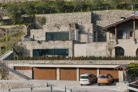 Naturstein aus der Region prägt das terrassiert im Hang liegende private Wohnhaus mit Blick auf das Tal / Bildnachweis: Andrea Puliogotto
