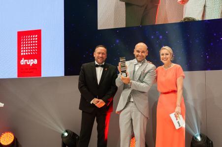 Pablo Kern, Prokurist bei Meyle+Müller (Mitte) nimmt den Award zum Crossmedia-Dienstleister des Jahres vom Moderatorin Ruth Moschner und Christian Hruschka Messe Düsseldorf, DRUPA, entgegen