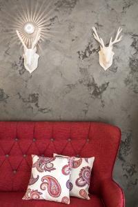 """Blickfang im Foyer: rotes Sofa vor dunkelbrauner Akzentwand mit metallisch schimmernder Oberflächenbeschichtung (Metallocryl """"Perle"""" Palazzo 125)  (Foto: Caparol Farben Lacke Bautenschutz/Martin Duckek)"""