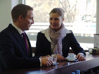 Suchen noch zusätzliche Kollegen: zwei Mitarbeiter der SELLBYTEL Group beim Austausch an der unternehmenseigenen Kaffeebar