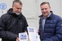 """Rolf Klenk, Arbeitsgemeinschaft Fledermausschutz Rheinland-Pfalz, übergibt Dominik Kauss, Süwag-Mitarbeiter, die Urkunde """"Fledermäuse willkommen""""."""