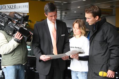 Andreas Mücke, Geschäftsführer des Autohaus VW Dunker bei den Dreharbeiten mit Jackie Weiss und RTL-Moderator Cord Eickhoff (rechts)