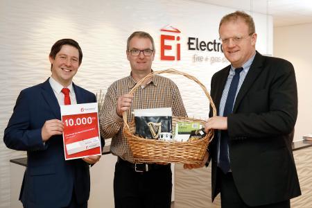 Geschäftsführer Philip Kennedy (r.) und Referent Robert Schmidt (l.) von Ei Electronics überreichten der zehntausendsten Fachkraft für Rauchwarnmelder Michael Rempe einen Präsentkorb mit irischen Spezialitäten