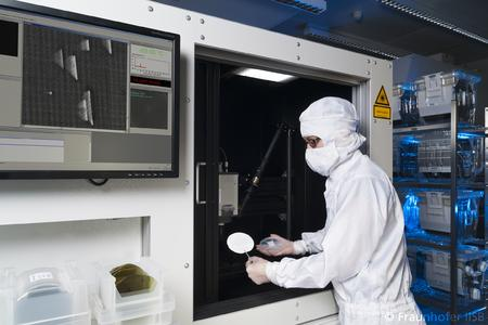 Operator loading a 100 mm SiC epiwafer in the defect luminescence scanner at Fraunhofer IISB
