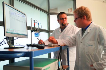 Dr. Robert Gerke (links) und Dr. Mathias Schnippering besprechen die Ergebnisse einer Elektrolyt-Untersuchung, durchgeführt mit einem Potentiostaten.