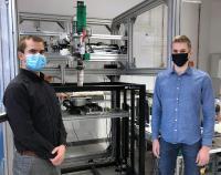 Gruppenleiter Michel Layher (links) und Lukas Eckhardt vom Bereich Additive Fertigung der EAH Jena vor dem 3D-Drucker für großvolumiges Schmelzschichten