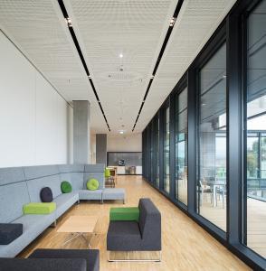 Im Innenraum gelangen Mitarbeiter und Besucher zunächst in den großzügig gestalteten Empfangsbereich / Bildnachweis: Schüco International KG // Fotograf: Atelier Altenkirch