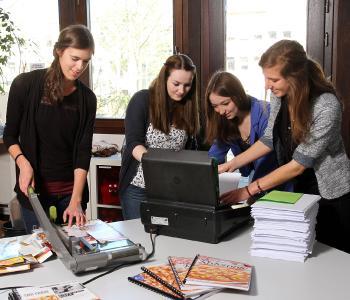 Die Studentinnen (von links nach rechts) Teresa Körber, Julie Vesque, Laura Sterle und Janika Ofterdinger stellen Blöcke aus einseitig bedrucktem Papier und Verpackungskartons her / Foto: Thomas Koziel