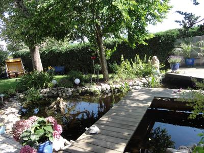 Ein verspielter Gartenteich- der schmale Holzsteg über den Teich führt zum prominent gelegenen Sitzplatz am Wasser. Der Buddha in der Pflanzung betont und unterstreicht das friedliche Gartenbild aus Wasser- Pflanzen- Holz und Stein