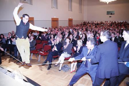 Mut tut gut – den Beweis trat Johannes Warth im Bad Mergentheimer Kursaal auch selbst mehrfach an: wie hier auf dem Seil – getragen von den Mitarbeiter der WITTENSTEIN AG – darunter auch Vorstandssprecher Karl-Heinz Schwarz (erster der Gruppe am Seil);  sitzend, 1. Reihe : Dr. Manfred Wittenstein, Vorstandsvorsitzender der WITTENSTEIN AG