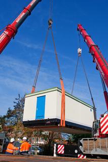 Zwei Spezialkräne heben die über 50 Tonnen schwere Schaltstation der WEMAG vom Tieflader und setzen sie auf das vorbereitete Fundament. Foto: WEMAG/Rudolph-Kramer