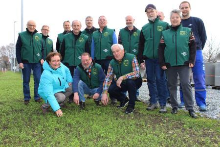 """Kerstin Ihlenfeldt-Wulfes (vorne links) und die Naturschutzgruppe """"Wühlmäuse"""" blicken positiv auf das erste Wachstumsergebnis des neu angesäten Blühstreifen auf dem DOYMA Betriebsgelände"""