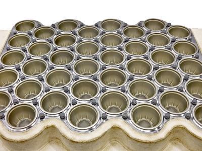 Thermoformwerkzeug zur Produktion von Polypropylen-Bechern. Die olivfarbene HART-COAT®-Schicht ist auf den Formen gut zu erkennen