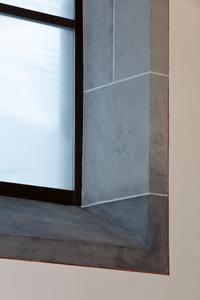 Die Fenster erhielten die Optik einer Steineinfassung, die aufgemalt wurde. Zur optischen Annäherung an natürliche Steine tupften die Maler die verschiedenen Lasurfarbtöne mit dem Schwamm übereinander und zeichneten die Fugenlinien auf (Foto: Caparol Farben Lacke Bautenschutz/Cornelia Suhan)