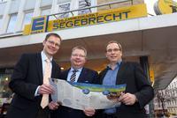 Harald Halfpaap (l.) und Udo Sahling (r.)  gratulieren Jens Segebrecht (m.) zu seinem vorbildlich modernisierten Supermarkt, einem guten Beispiel aus der Beratungskampagne e.coBizz
