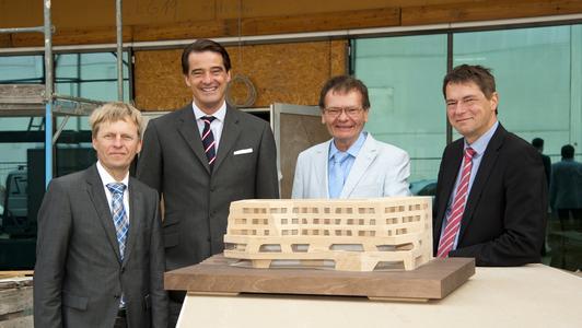 (v.l.): Rüdiger Kruse, Pieter Wasmuth, Wolfgang Pages und Dr. Oliver Weinmann auf der Baustelle hinter einem Modell des Wälderhauses. Zusammen besichtigten sie das Gebäude