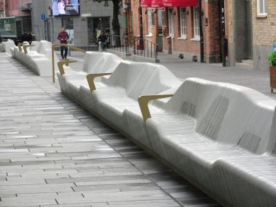 Aus der organischen Form der Sitzbank stechen ab und zu metallisch glänzende Lamellen hervor, die Armlehnen erzeugen.