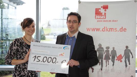 Nadine Otta, verantwortlich für das Fundraising der DKMS, nimmt den Spendenscheck über 15.000 Euro von Mirko Herrmann, Leiter Marketing & Communications der SER-Gruppe, in Empfang.