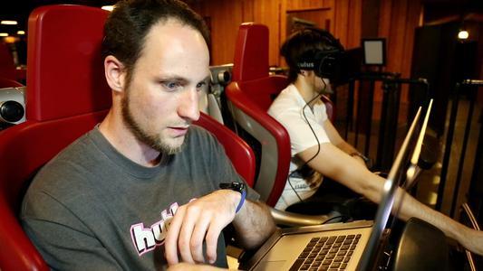 Maximilian Winter (links) begleitet David Kebrich (rechts) während der Achterbahnfahrt am Laptop und überwacht die Synchronität zur virtuellen Welt