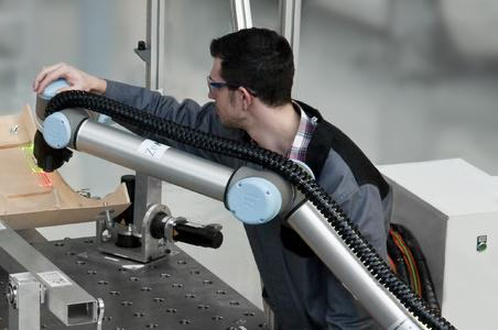 Laser-based assistance in man-robot cooperation. The LAP CAD-PRO laser projector marks the positions at which the worker has to place the stringers on the CFC shell.  (Foto: ZeMA)