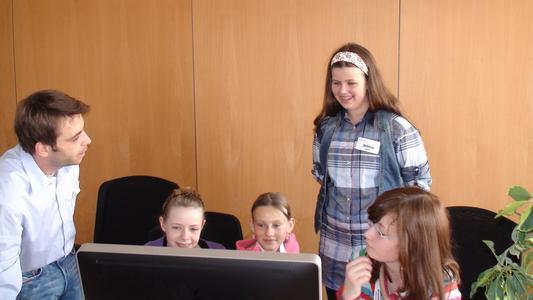 Mauro Niro (links) zeigt den Mädchen das Online-Wahlsystem POLYAS