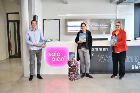 Conny Roth (Mitte) und Regine Bücker (rechts) vom Kinderschutzbund Kempten e.V. mit Christoph Breher (Soloplan) bei der Übergabe der Bastelbücher in Soloplan City.