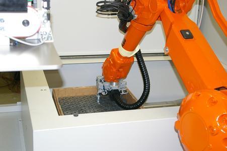 Ein teilespezifisches Programm steuert sowohl die Roboterbewegungen und den selbstständigen Tausch des Greifers durch den Roboter als auch die über den Palettenstationen an der Zellendecke angebrachten Kameras.