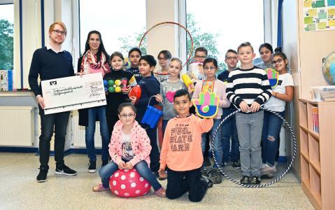 Die Kinder der Heiligenwegschule mit ihrer Schulleiterin Julia Germelmann freuen sich über die Spende von secova. Überreicht wurde sie durch secova-Mitarbeiter Jan Hasse - der Osnabrücker hatte die Schule als Spendenempfänger vorgeschlagen.