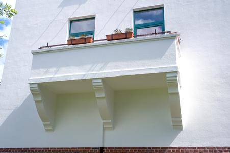 Nach dem Einblasen von Mineralwolle zwischen die beiden Mauerschalen erhält die Oberfläche von Fassade und Balkon mit dem Caparol-Anstrichsystem AmphiSilan dauerhaften Schutz und ursprüngliche Schönheit (Foto: Caparol Farben Lacke Bautenschutz/Foto Penz)