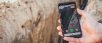 Ein Smartphone über einem offenen Baugraben. Mit der Vaira App wird gerade eine Vermessung in Augmented Reality durchgeführt.